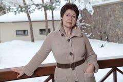 Mujer mayor atractiva que presenta en terraza al aire libre en invierno Imágenes de archivo libres de regalías