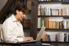 Mujer mayor atractiva que trabaja en la computadora portátil Foto de archivo libre de regalías