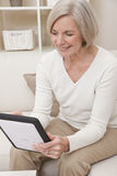 Mujer mayor atractiva que usa un ordenador de la tablilla Imágenes de archivo libres de regalías