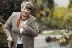Mujer mayor con el bastón durante ataque de la disnea fotografía de archivo