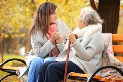 Mujer mayor con el bastón y el cuidador joven que se sientan en banco Fotografía de archivo libre de regalías