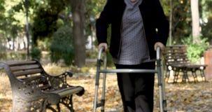 Mujer mayor con el caminante que se levanta y que camina al aire libre almacen de video