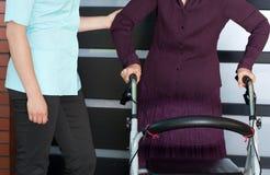 Mujer mayor con el caminante y la enfermera ortopédicos Imagenes de archivo