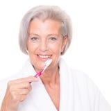 Mujer mayor con el cepillo de dientes fotos de archivo