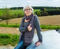 Mujer mayor con el coche y los pulgares para arriba Fotos de archivo