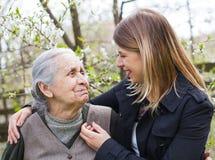 Mujer mayor con el cuidador alegre al aire libre, primavera Imagenes de archivo