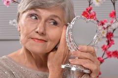 Mujer mayor con el espejo imagenes de archivo