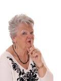Mujer mayor con el finger sobre boca Imágenes de archivo libres de regalías