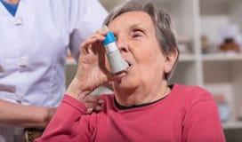 Mujer mayor con el inhalador del asma Foto de archivo libre de regalías