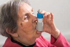 Mujer mayor con el inhalador del asma Foto de archivo
