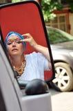 Mujer mayor con el jewlery indio que mira el mirrow del coche en el s Imagen de archivo libre de regalías