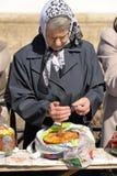 Mujer mayor con el kulitch de pascua y vela en los monas de Spaso-Uspensky Imagenes de archivo