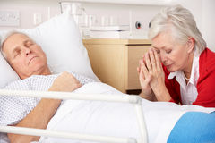 Mujer mayor con el marido seriamente enfermo imagenes de archivo