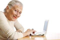 Mujer mayor con el ordenador portátil Imagenes de archivo