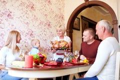 Mujer mayor con el pavo asado para una familia de celebración en un fondo ligero Concepto de la tradición Copie el espacio Imagen de archivo