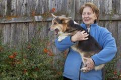 Mujer mayor con el perrito del corgi imagenes de archivo