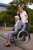 Mujer mayor con el sillón de ruedas Imagenes de archivo