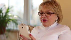 Mujer mayor con el smartphone blanco almacen de video