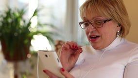 Mujer mayor con el smartphone blanco almacen de metraje de vídeo