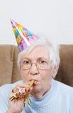 Mujer mayor con el sombrero del cumpleaños y el fabricante del ruido Imagenes de archivo