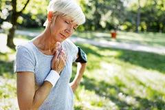 Mujer mayor con el sufrimiento del dolor de pecho del ataque del corazón durante activar foto de archivo libre de regalías