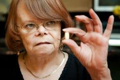 Mujer mayor con el suplemento diario Imagenes de archivo