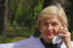 Mujer mayor con el teléfono fotos de archivo libres de regalías