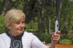 Mujer mayor con el teléfono de la cámara Fotos de archivo