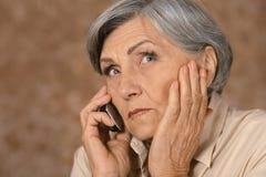 Mujer mayor con el teléfono móvil imagen de archivo