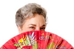 Mujer mayor con el ventilador rojo del dragón Imagen de archivo