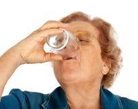 Mujer mayor con el vidrio de agua Imagen de archivo libre de regalías