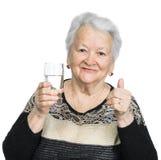 Mujer mayor con el vidrio de agua Imagen de archivo