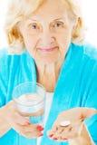 Mujer mayor con el vidrio y la tableta de agua Foto de archivo