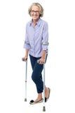 Mujer mayor con gafas que camina con las muletas Fotos de archivo libres de regalías
