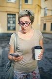 Mujer mayor con la bebida usando smartphone imágenes de archivo libres de regalías