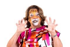 Mujer mayor con la cara-pintura del tigre imagenes de archivo