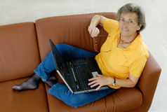 Mujer mayor con la computadora portátil imagen de archivo