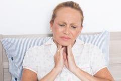 Mujer mayor con la garganta dolorida fotografía de archivo