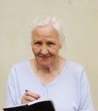 Mujer mayor con la hoja de trabajo Fotos de archivo libres de regalías