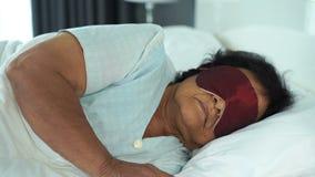 Mujer mayor con la máscara de ojo que duerme en una cama almacen de metraje de vídeo