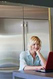 Mujer mayor con la mano en la barbilla usando el ordenador portátil Fotos de archivo libres de regalías