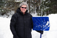 Mujer mayor con la pala de la nieve Imagen de archivo