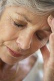 Mujer mayor con la pista en las manos que parecen cansadas Imagen de archivo libre de regalías