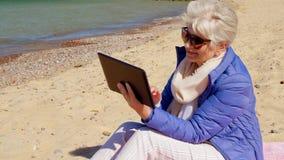 Mujer mayor con la tableta en la playa metrajes