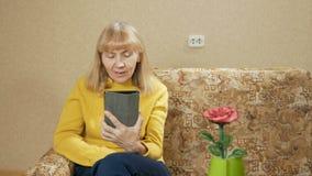 Mujer mayor con la tableta que se sienta en el sofá en sala de estar Habla la comunicación video con los parientes Él está sonrie almacen de video