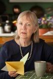 Mujer mayor con la tarjeta de condolencia Imagen de archivo libre de regalías
