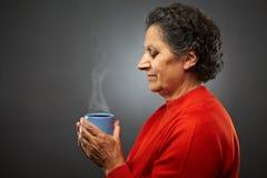 Mujer mayor con la taza caliente de té Imagenes de archivo