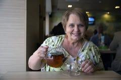 Mujer mayor con la taza de té en café Imagen de archivo