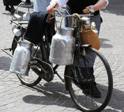 mujer mayor con las latas viejas de la bicicleta y de la leche Imagen de archivo