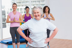 Mujer mayor con las manos en la cadera que se coloca en gimnasio fotos de archivo libres de regalías